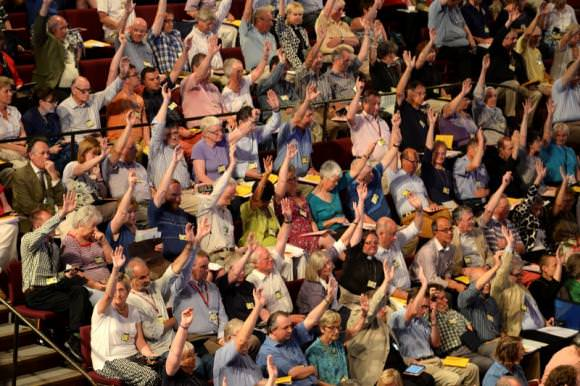 Members of the Church of England's Synod vote on one of the motions during the session during which approved the consecration of women bishops, in York